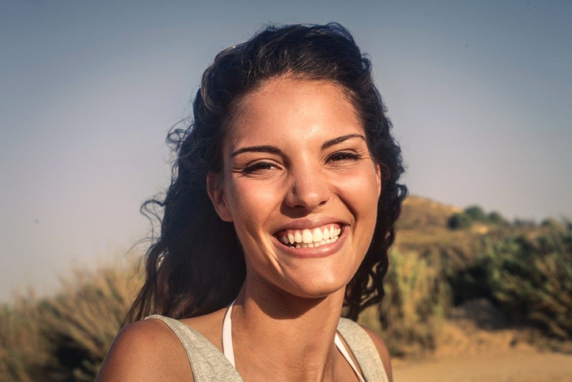 woman with bright white smile outdoors