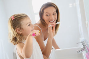 mom brushing teeth with child