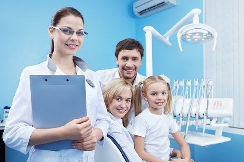 family standing with dentist